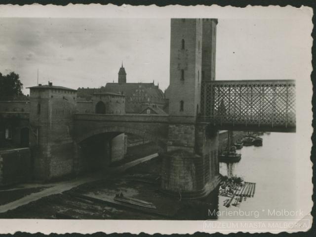 Fotografia przedstawia bramę mostową – wjazd na most drogowy na Nogacie po północnej stronie zamku krzyżackiego. W tle widoczne są zabudowania zamkowe.