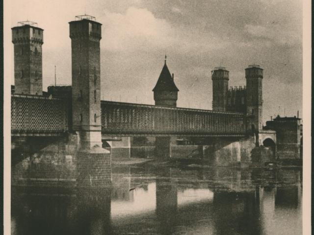 Fotografia przedstawia most drogowy na Nogacie po północnej stronie zamku krzyżackiego z charakterystycznymi basztami mostowymi. W tle widoczny fragment Baszty Maślankowej należącej do zespołu zamkowego.