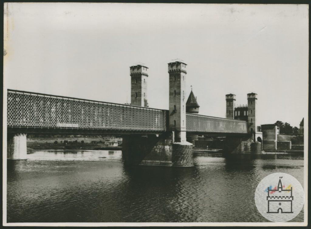 Fotografia przedstawia most drogowy na Nogacie po północnej stronie zamku krzyżackiego z charakterystycznymi basztami mostowymi. W tle widoczny dach Baszty Maślankowej należącej do zespołu zamkowego.