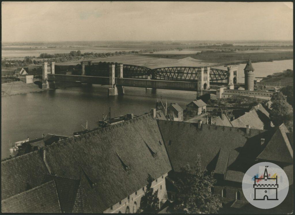 Fotografia przedstawia widok północny z wieży zamku krzyżackiego na dwa mosty – kolejowy i drogowy – na Nogacie. U dołu zdjęcia znajdują się zabudowania skrzydła północnego i zachodniego Zamku Średniego oraz zabudowa miejka na bulwarze przy Nogacie. W tle widoczny jest płaski teren Żuław.