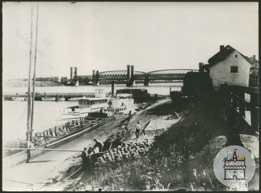 Fotografia przedstawia widok na kładkę pieszą, most drogowy oraz kolejowy na rzece Nogat po północnej stronie krzyżackiego zamku. Z prawej strony widoczny dom należący do zabudowy miejskiej.