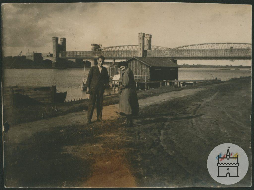 Fotografia przedstawia dwa mosty – kolejowy i drogowy – na Nogacie, po północnej stronie zamku krzyżackiego. Na pierwszym planie widać kobietę i mężczyznę, w eleganckim odzieniu, pozujących do fotografii na prawym brzegu Nogatu.