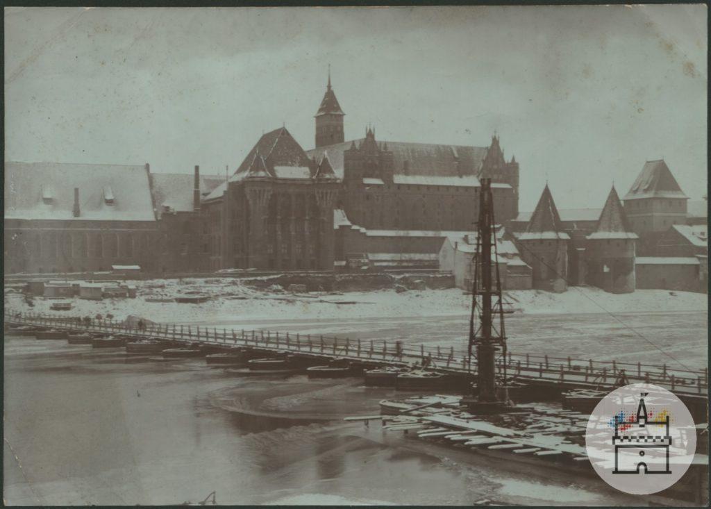Fotografia przedstawia zimowy obraz zachodniej części zespołu zamku krzyżackiego. Na pierwszym planie znajduje się zamarznięta rzeka Nogat z kładką pieszą łączącą dwa brzegi. W tle zaśnieżone dachy zamkowe.